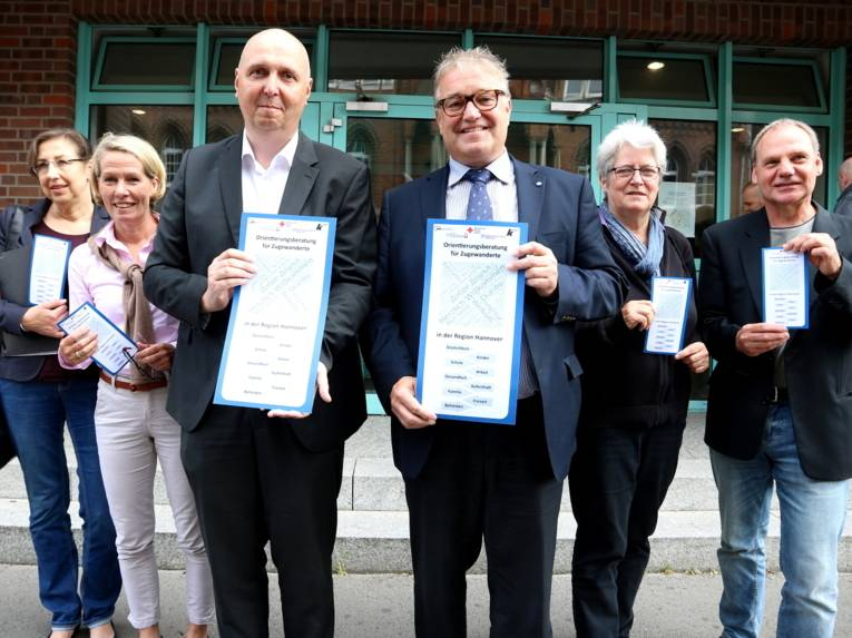 Vier Personen stehen nebeneinander und halten einen Flyer in ihren Händen.
