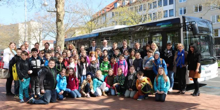 Achtzehn Erwachsenen und etwa vierzig Kinder haben sich in mehreren Reihen draußen vor einem seitlich parkenden Bus positioniert.
