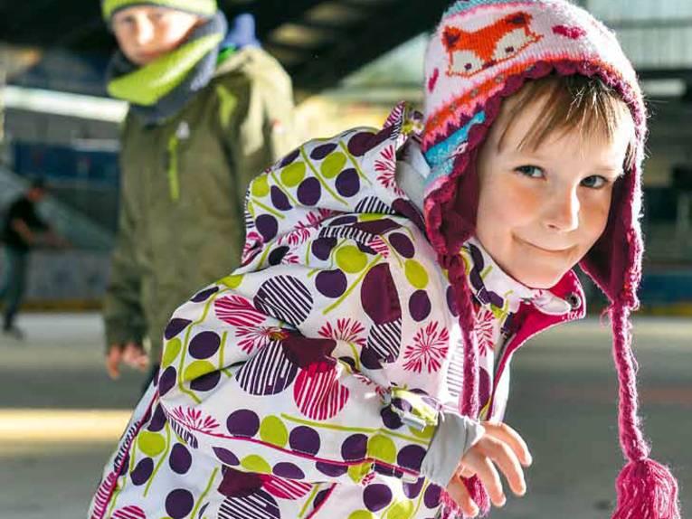 Ein Mädchen und ein Junge unterbrechen kurz den Schlittschuhlauf und blicken in die Kamera.