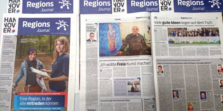 Mehrere RegionsJournale liegen übereinander verschachtelt auf einem Tisch, von einem Exemplar ist das Titelblatt zu sehen, ein weiteres liegt aufgeschlagen rechts daneben.