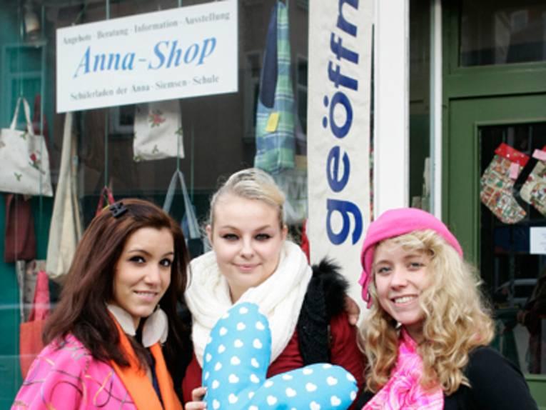 """Drei junge Frauen mit selbstgemachten Produkten vor dem """"Anna-Shop"""", indem sie ihre selbst hergestellten Waren verkaufen."""