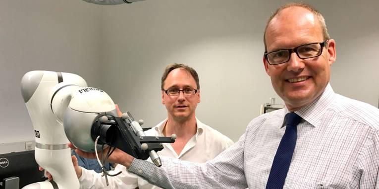 Zwei Männer stehen neben einem Roboterarm.