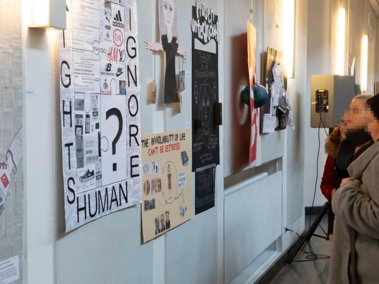 Exponate an einer Wand, die von drei Frauen angesehen werden.