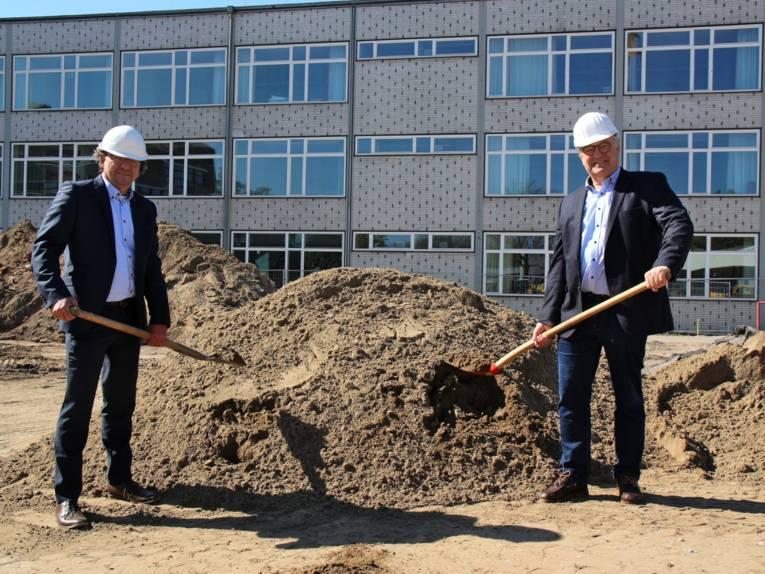 Zwei Männer mit Spaten vor einem Sandberg. Im Hintergrund befindet sich ein Gebäude.
