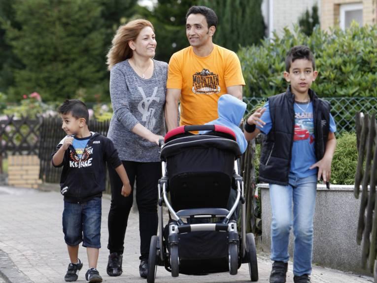 Eine Familie geht spazieren, der jüngste der drei Söhne wird im Kinderwagen geschoben.