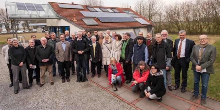 Gruppe von Personen vor einem Haus mit Solarzellen auf dem Dach