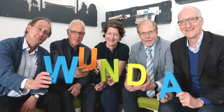"""Vier Männer und eine Frau sitzen und halten die Buchstaben """"WUNDA""""."""