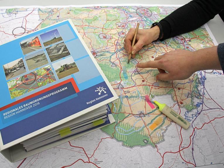 Aktenordner, Landkarte, eine Hand, die einen Bleistift hält, eine Hand, die einen gelben Textmarkter hält