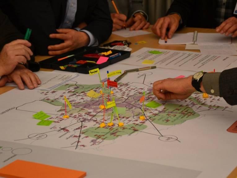 Auf einem Tisch liegende Karte, auf der Fähnchen und Aufkleber platziert sind, Hände von Menschen, die rund um den Tisch sitzen und an dieser Karte arbeiten
