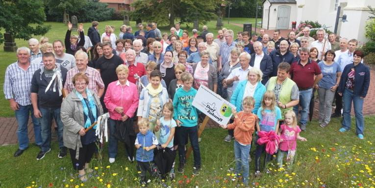 """Mehrere Personen lassen sich mit einem Schild fotografieren, darauf steht """"Unser Dorf hat Zukunft"""". Bundeswettbewerb 2016. Dudensen. Außerdem ist das Ortswappen von Dudensen angebracht, es zeigt eine Windmühle und Kornähren und die Farben Grün und Gelb."""