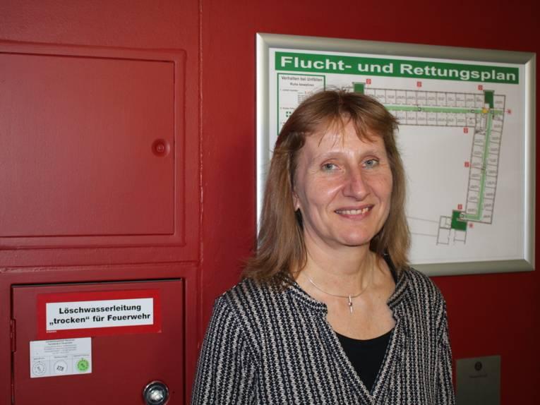 Eine Frau steht vor einer roten Wand.