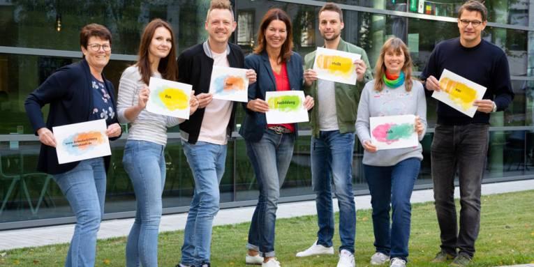 Vier Frauen und drei Männer stehen nebeneinander und halten jeweils ein DIN A4 Schild in den Händen.