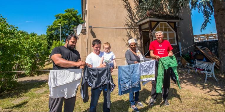 Drei Männer und eine Frau hängen Wäsche zum Trocknen auf eine Leine, im Hintergrund ist ein Wohnhaus. Der zweite Mann von Links hält dabei einen kleinen Jungen auf dem Arm.