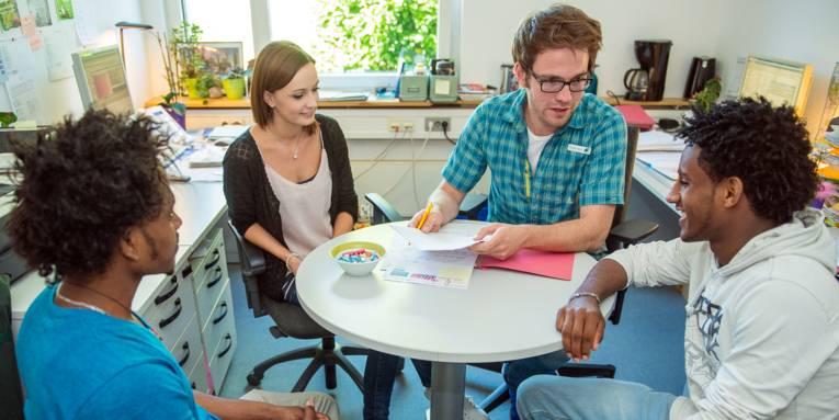 Drei Männer und eine Frau sitzen an einem runden Tisch.