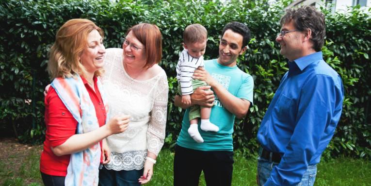 Vier Erwachsene und ein Kleinkind stehen in einem Garten.