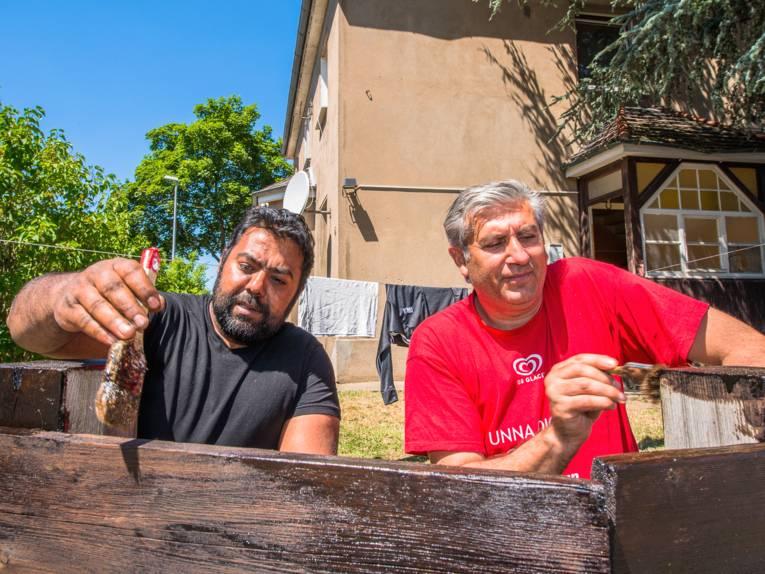 Zwei Männer streichen einen Zaun.