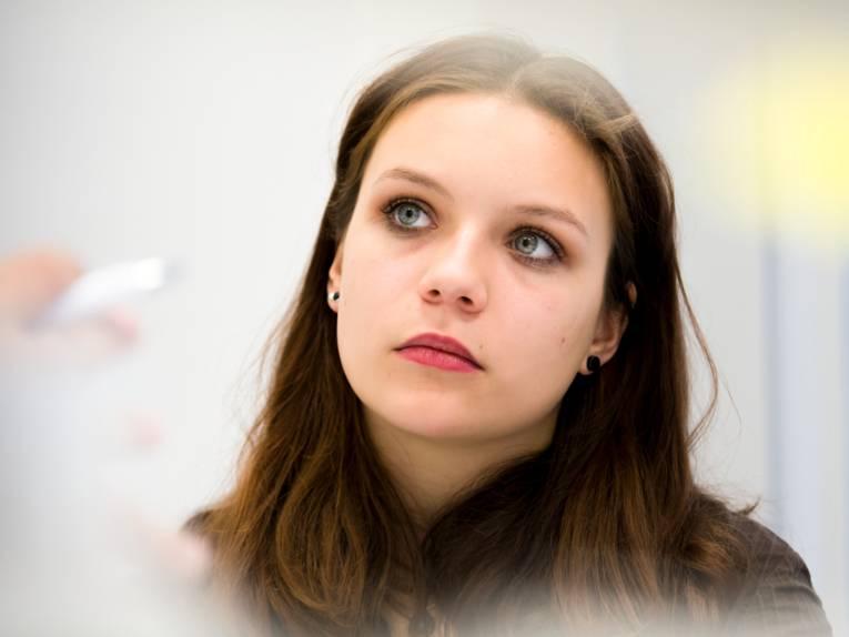 Eine junge Frau schaut gedankenverloren in die Kamera.
