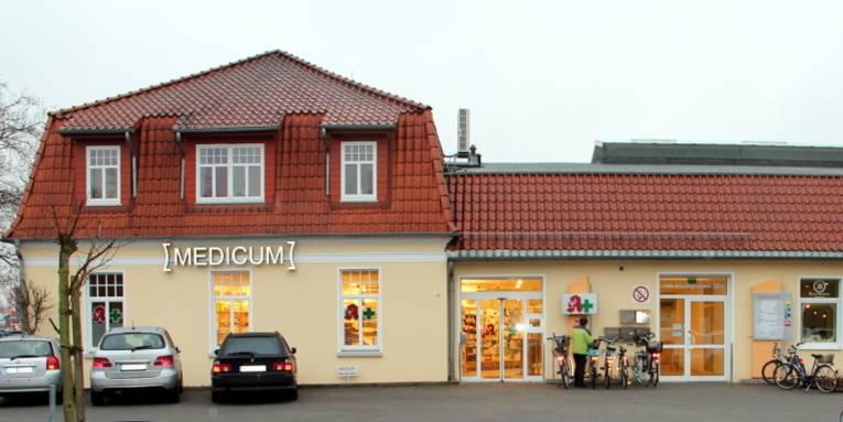 Zweigeschossiges Gebäude mit rotem Ziegeldach und gelber Fassade. Vor dem Ärztehaus sind Autos und Fahrräder abgestellt. Leuchtbuchstaben sind an der Fassade angebracht, sie bilden das Wort [MEDICUM].