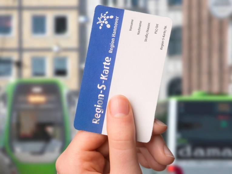 Eine Hand hält die Region-S-Karte, im Hintergrund sind Fahrzeuge des Öffentlichen Personen Nahverkehrs (ÖPNV) zu sehen.