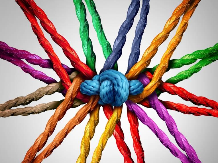Verschiedenfarbige Seile, die von einem geknoteten Seil in der Mitte zusammengehalten werden