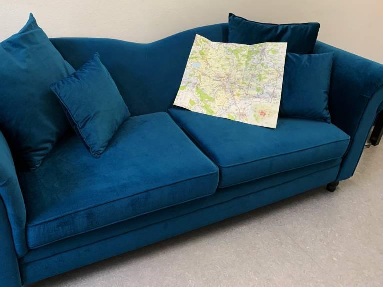 Ein blaues Sofa auf dem eine Karte liegt.