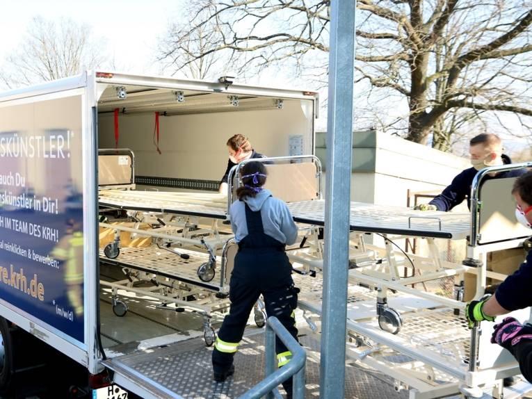 Menschen mit Masken laden Krankenhausbetten in einen LKW