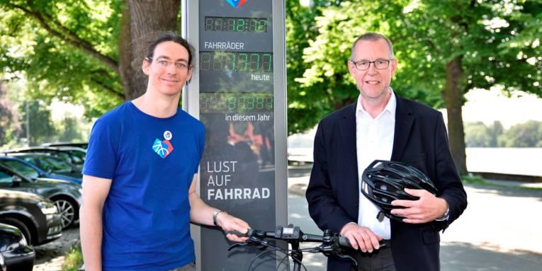 Zwei Männer stehen am Maschsee vor der dritten Fahrradzählstation im Gebiet der Stadt Hannover.
