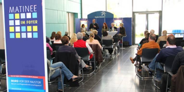Publikum sitzt in Stuhlreihen vor einem Podium, das aus Bistrostühlen und Stehtischen besteht.