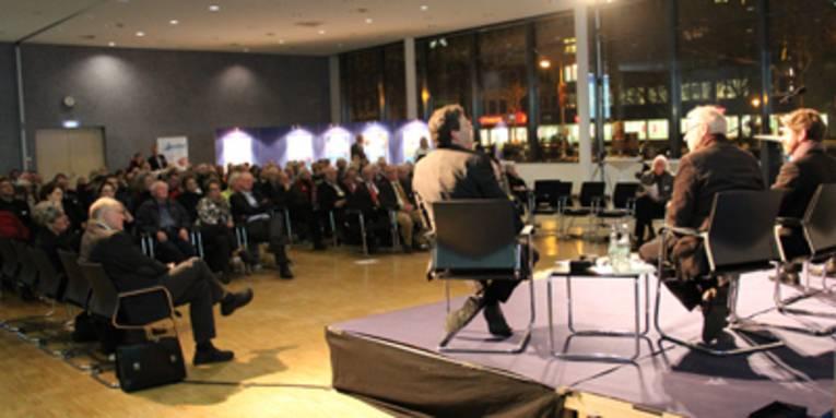Zuschauer sitzen abends in einem beleuchteten Sitzungssaal und schauen auf eine kleine Bühne, auf der zwei Männer Platz genommen haben.