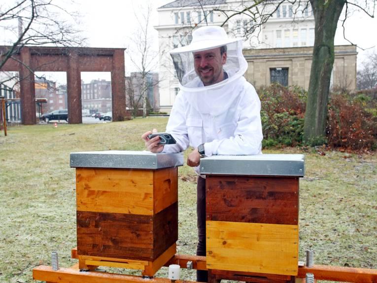 Ein Mann mit Schutzkleidung hat ein Smartphone in der Hand und steht hinter zwei Bienenstöcken.