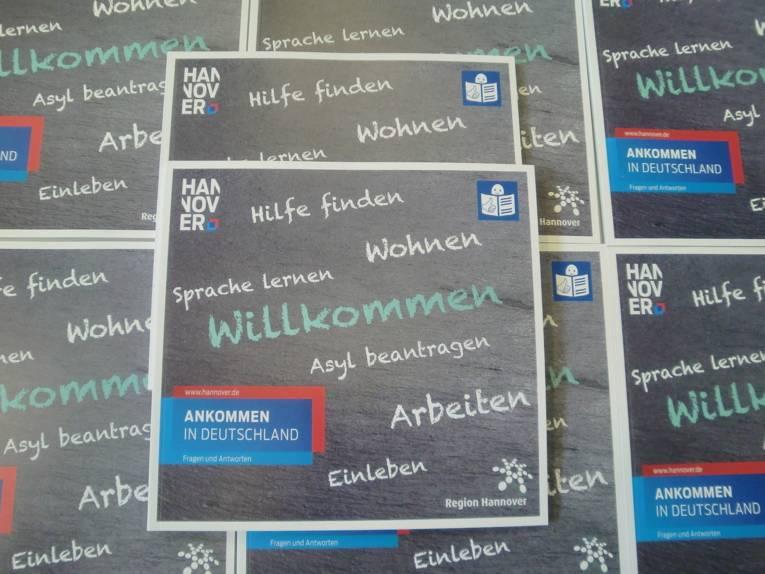 """Exemplare der Broschüre """"Ankommen in Deutschland – Fragen und Antworten"""" liegen aufeinander."""