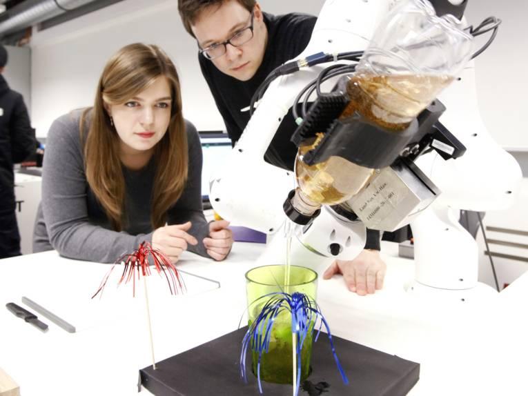 Ein Mann und eine Frau schauen auf einen Roboterarm, dieser gießt gerade eine Flüssigkeit aus einer Flasche in ein Cocktailglas.