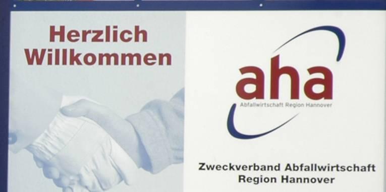 """Schild mit der Aufschrift """"Herzlich Willkommen"""" und dem Logo der von """"aha"""""""