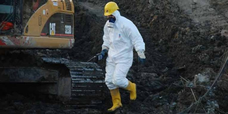 Person in einem weissen Arbeitsschutzanzug mit Atemmaske, gelben Helm und gelben Gummistiefeln