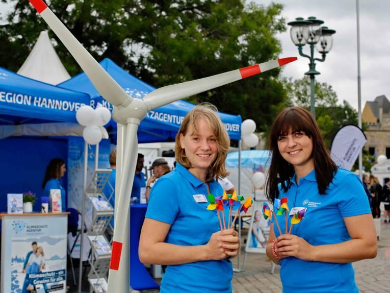 Zwei junge Frauen in blauen Poloshirts vor einem Miniaturwindrad und blauen Zelten
