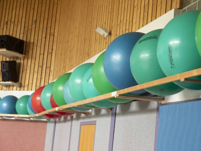Gymnastikbälle auf einer Ablage in einer Turnhalle