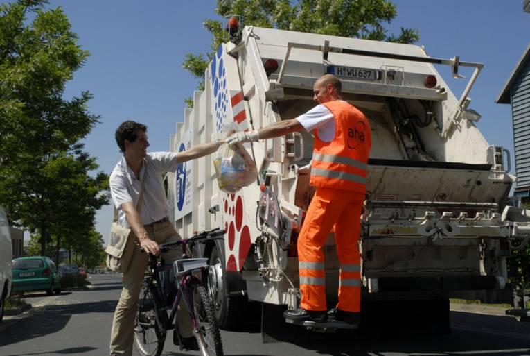 Fahrradfahrer reicht eine Mülltüte einem Mitarbeiter der Müllabfuhr