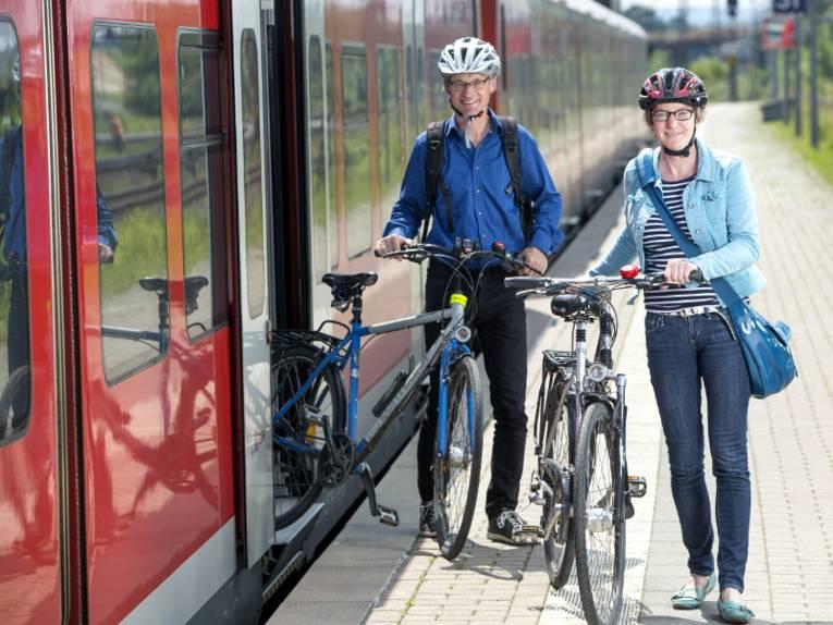 Eine Frau und ein Mann schieben ihre Fahrräder aus einer S-Bahn.