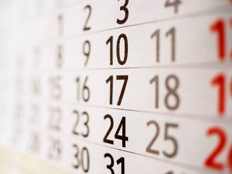 Ein Ausschnitt eines weißen Wandkalenders, auf dem die Zahlen in schwarz und teilweise rot abgebildet sind.