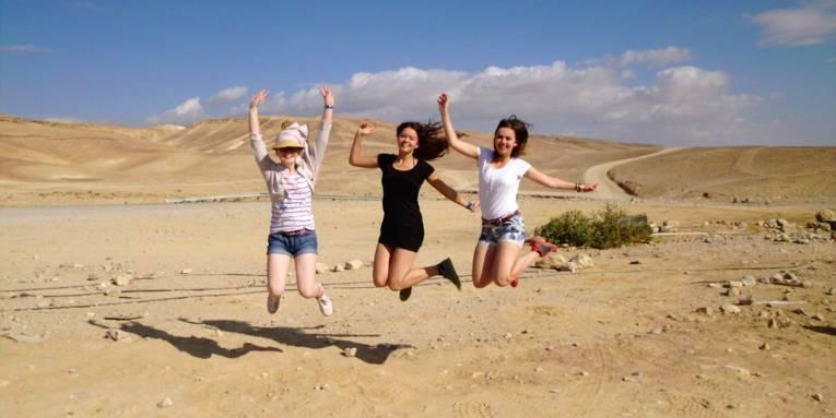 Drei Mädchen sind in einer Wüste und springen in die Luft.
