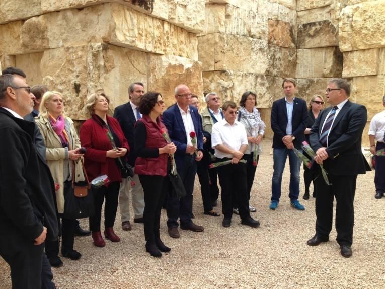 Die Gruppe der Delegationsteilnehmer vor Wänden aus großen Steinquadern. Viele halten eine rote Rose in der Hand.
