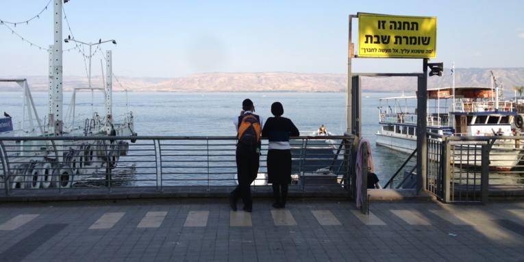 Zwei Personen stehen an einer Uferpromenade und blicken auf einen See