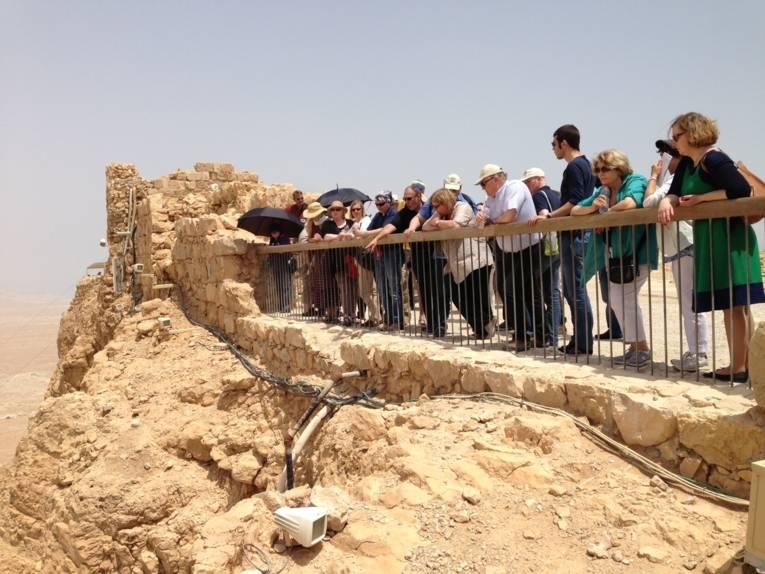 Eine Gruppe von Personen steht an einer Festungsmauer