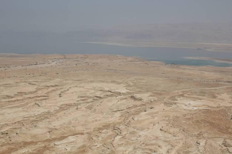 Blick über eine Wüstenlandschaft auf ein grosses Gewässer