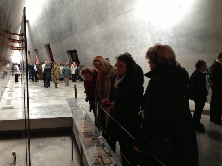 Eine Gruppe von Personen in einer Halle, die Exponate betrachten.