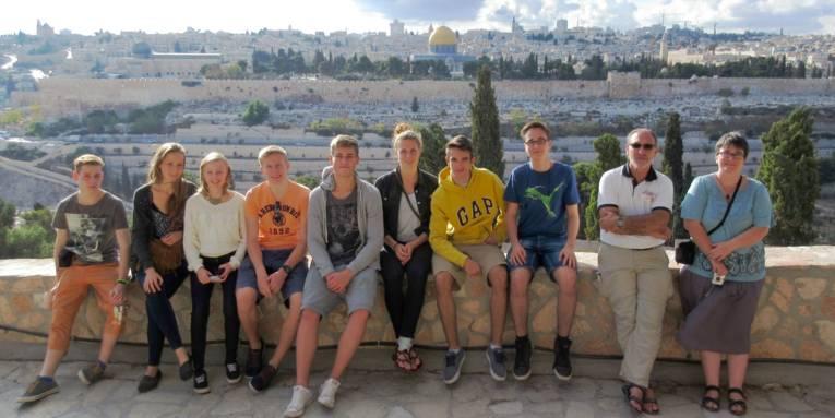 Zehn Personen sitzen auf einer Mauer, im Hintergrund sind Gebäude der Stadt Jerusalem zu sehen.