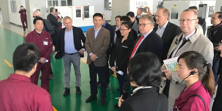 Eine Besuchergruppe steht in einer Fabrikhalle.