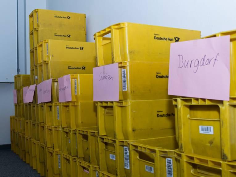 Mehrere gelbe Kisten - an einigen von ihnen hängt ein Zettel.