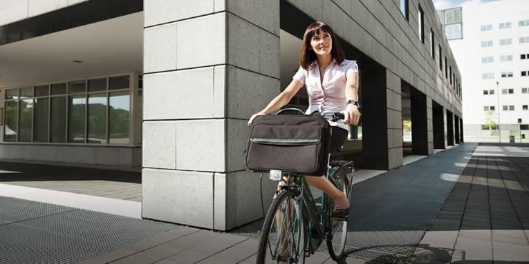 Geschäftsfrau auf einem Fahrrad vor Bürogebäuden