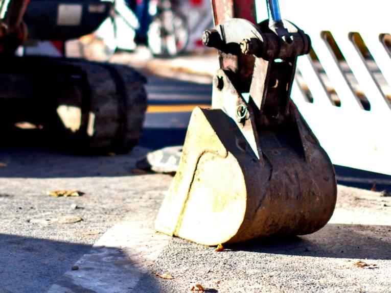 Die Baggerschaufel eines Baggers ruht auf Untergrund.